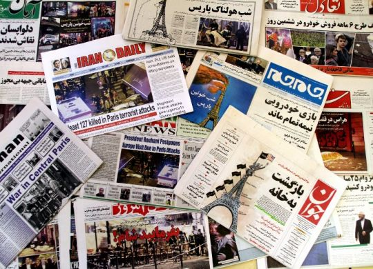 """A photo taken on November 15, 2015 in the Iranian capital Tehran shows newspapers bearing the headlines of the deadly Paris attack that left more than 120 people dead, in the worst such violence in France's history. Most Iranian papers dedicated their front pages to terror attacks in Paris that killed at least 129, as conservative papers said France was paying for its policies in Syria. Ultraconservative Vatan-e Emrooz (bottom) printed """"Dinner is ready"""" over the picture of a dead body covered by a white sheet and empty cafe chairs in the background, while a masked jihadist with a gun and a machete was pictured on top of the Eiffel tower in hardliner Javan daily cover (C-R), rasing a mixed flag of the United States and IS while flashing a victory sign. AFP PHOTO / ATTA KENARE"""
